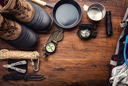 Outdoor travel equipment planning for a mountain trekking camping trip on wooden background. Top view - vintage film grain filter effect styles