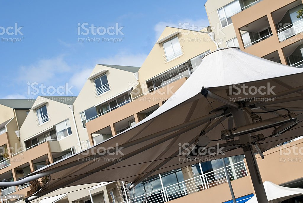 Outdoor umbrella and modern apartment buildings stock photo