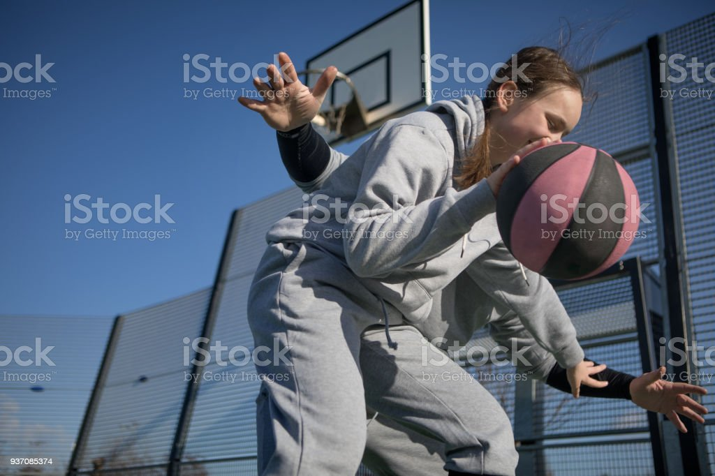 Outdoor urban basketball training session between male father coach...