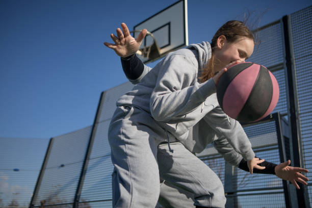 Outdoor urban basketball training session between male father coach and female daughter player stock photo