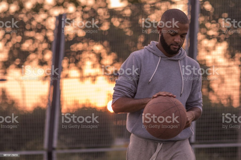 Outdoor urban basketball training session for a young male streetball...