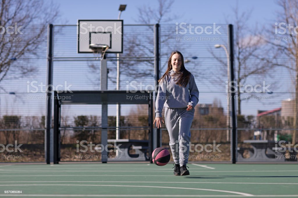 Outdoor urban basketball training session for individual female...