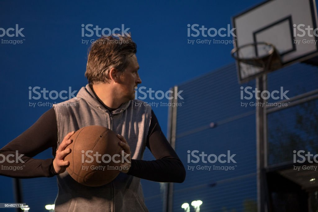 Outdoor urban basketball training session for individual middle aged...