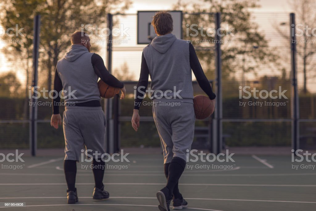 Outdoor urban basketball training session for two middle aged male...