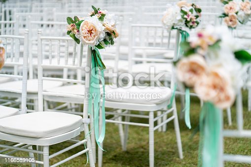 Outdoor wedding venue chairs with flower and teal color ribbon decoration