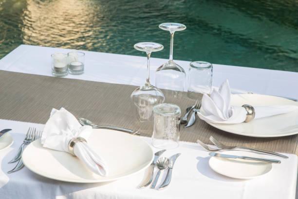 weißer tisch im freien für das mittagessen mit leeren tellern - geheime garten parties stock-fotos und bilder