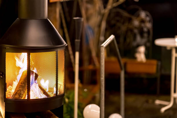 outdoor wood stove with burning open fire (nighttime) stock photo