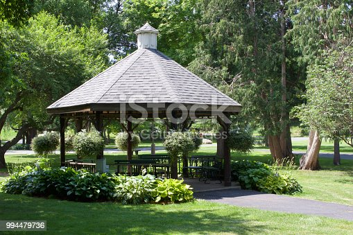 This image shows a brown wooden gazebo with landscaping around it in a city or town park setting.