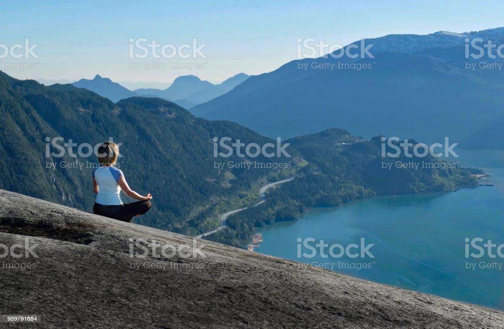 Outdoor-Yoga-Retreat. Frau in Lotus Pose meditieren auf Berggipfel mit schöner Aussicht. – Foto