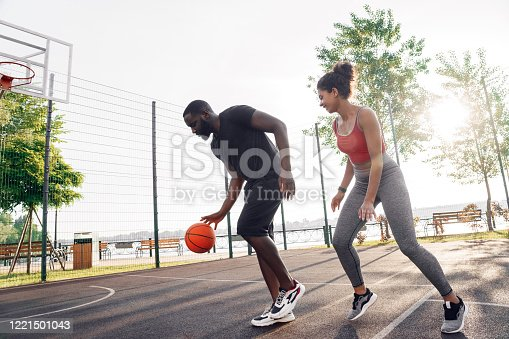 Young african descent couple man dribbling while woman defencing backdoor smiling happy on basketball court outdoors in sunlight