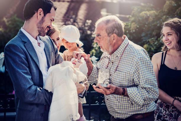 outdoors baby baptism with family and celebrant. - крещение стоковые фото и изображения