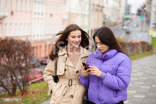 Outdoors close-up portrait of two 17 year old teenage girls with long brown hair with mobile phone