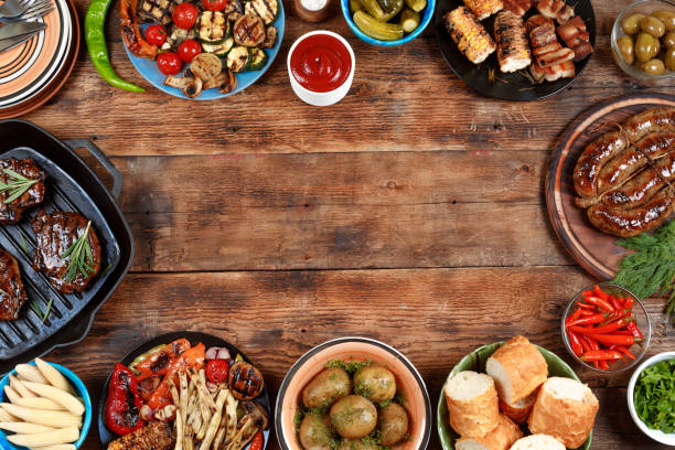 Outdoors Food Concept. Delicious barbecued steak, sausages and grilled vegetables on a wooden picnic table with copy space, top view stock photo