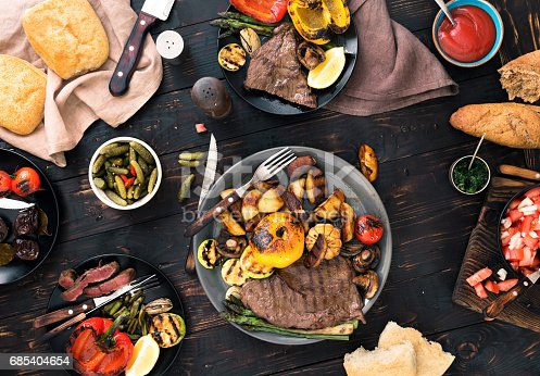 685404620istockphoto Outdoors Food Concept. Different dishes cooked on the grill, grilled steak and grilled vegetables on the wooden table 685404654
