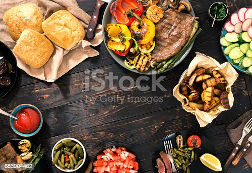 690274036 istock photo Outdoors Food Concept. Frame of Different foods cooked on the grill on the wooden table, grilled steak and grilled vegetables 683904462