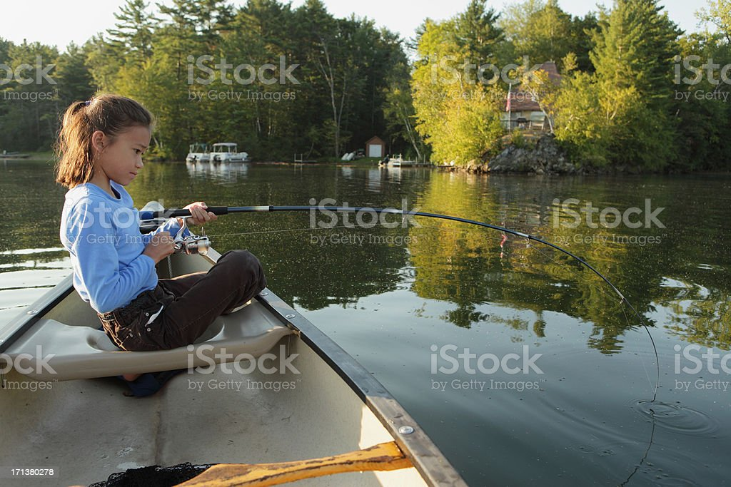 Outdoors girl fishing from a canoe on lake royalty-free stock photo