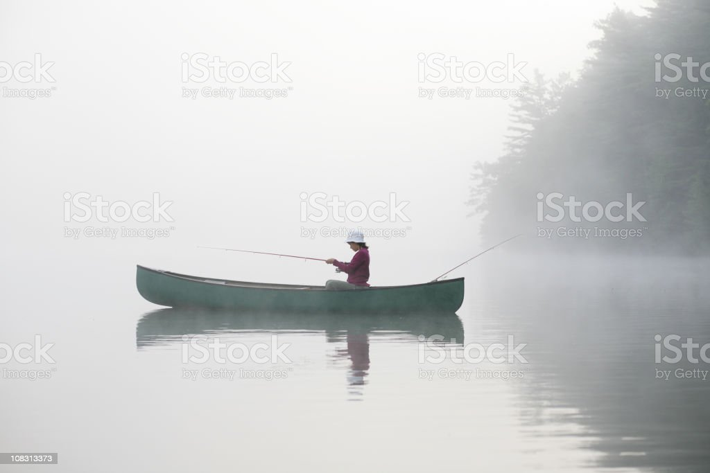 Outdoors girl fishing from canoe on lake in misty sunrise royalty-free stock photo