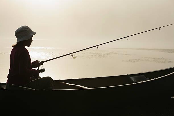 Im Freien Mädchen Angeln von Kanu auf nebligen See bei Sonnenaufgang – Foto