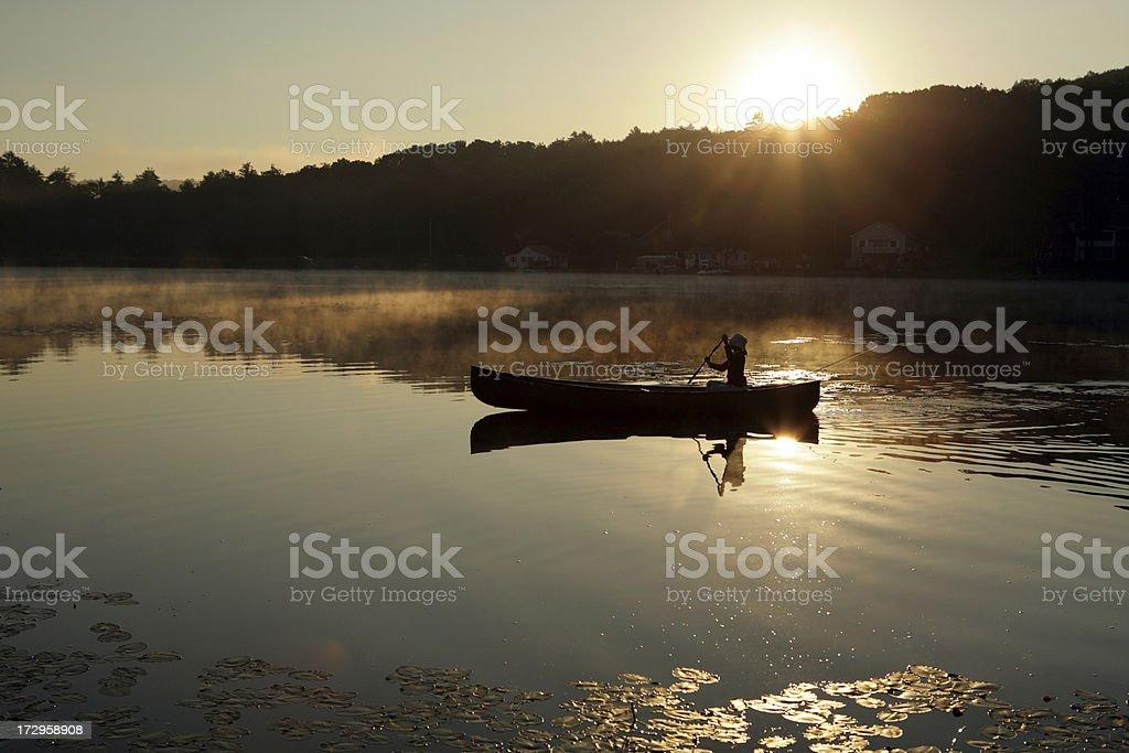 Outdoors girl paddling canoe on lake backlit sunrise royalty-free stock photo