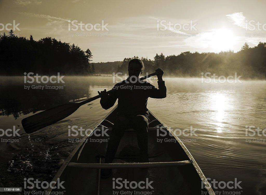 Outdoors girl paddling canoe on misty lake backlit sunrise sepia royalty-free stock photo