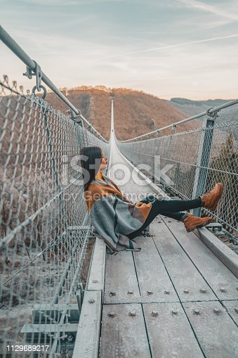 Photo of young woman sitting on a hanging bridge in Germany during the summer day, suspension rope bridge. Young female sitting alone outdoor and admiring view Travel Lifestyle concept with rope bridge background and sunset. Side view of Young woman on hanging rope bridge with sky as background. Leisure extreme activity at autumn day. Beautiful tourist on an excursion.
