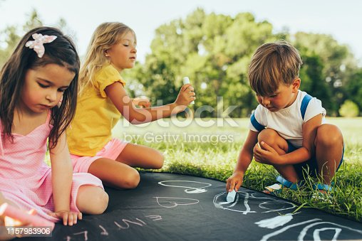 istock Outdoors image of kids sitting on the green grass playing with colorful chalks. Happy children drawing with chalks in the park. Friends, boy and two girls having fun on sunlight outdoor. Childhood 1157983906