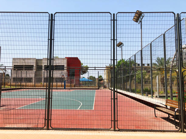 Outdoors mini football and basketball court with ball gate and basket surrounded with high protective fence. stock photo