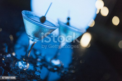 istock Outdoors night shot of two martinis with olives, as shot in Nassau. 879891696