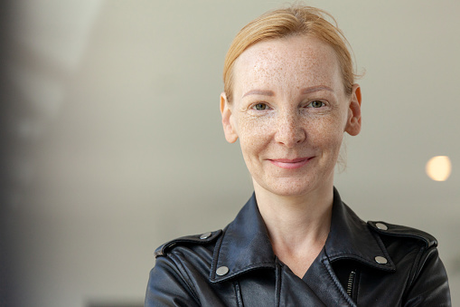 outdoors closeup portrait of a 45 year old red-haired woman in a black leather jacket