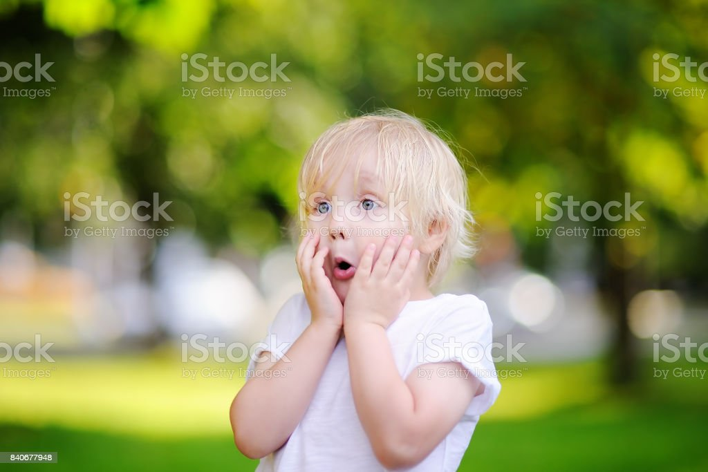 Outdoors portrait of cute suprised little boy stock photo