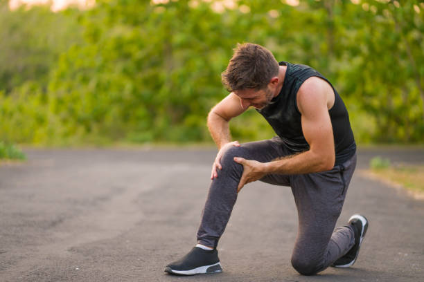 outdoors portrait of young attractive sport man in pain touching his knee suffering ligaments accident or some injury during running workout at beautiful country road in health care concept - giuntura umana foto e immagini stock