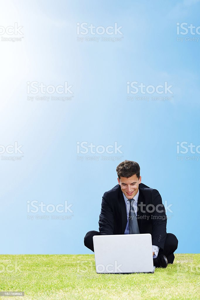 Outdoors working - Businessman on grass with a laptop royalty-free stock photo