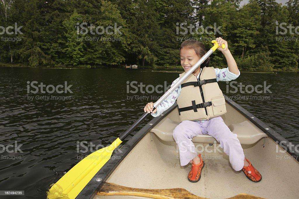 Outdoors young happy girl paddling canoe on lake royalty-free stock photo