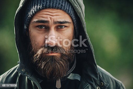 istock Outdor porttrait of a handsome brutal bearded man with dark beard and mustache dressed in winter clothes, covered with frost. Man wear coat hat and hood. look like hipster. 681978936