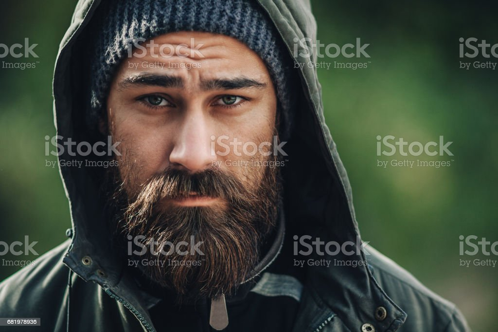 Outdor porttrait of a handsome brutal bearded man with dark beard and mustache dressed in winter clothes, covered with frost. Man wear coat hat and hood. look like hipster. stock photo