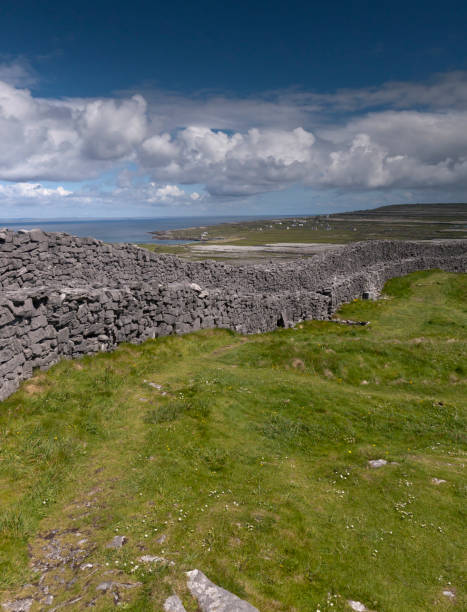 Outer Wall of Dun Aonghasa (Dun Aengus) with Island Landscape, Inishmore The view east, northeast from an outer enclosure of Dun Aonghasa (Dun Aengus) looking along the outer concentric wall, the exceptional dry stone and walkway visible.  Here the land falls away to review a view of Inishmore karst landscape, the coast and Galway Bay.  Note Dun Eochla on the distant ridge, to the right.  Aran Islands, County Galway, Ireland. michael stephen wills aran stock pictures, royalty-free photos & images