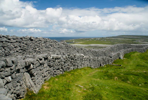 Outer Wall of Dun Aonghasa (Dun Aengus) with Island Landscape The view east, northeast from an outer enclosure of Dun Aonghasa (Dun Aengus) looking along the outer concentric wall, the exceptional dry stone and walkway visible.  Here the land falls away to review a view of Inishmore karst landscape, the coast and Galway Bay. michael stephen wills aran stock pictures, royalty-free photos & images