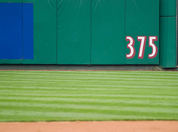Outfield Dimension A marker on the outfield wall of a baseball stadium indicates a dimension. padding stock pictures, royalty-free photos & images