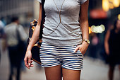 Outfit details of fashion elegant stylish woman posing. Female summer outfit with short striped blue and white shorts, grey t-shirt, modern leather backpack and golden jewelry and watch standing on city street.