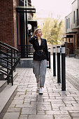 Outfit fashion, young stylish woman wearing oversized black jacket, grey jeans and trendy white sneakers. Urban fashion blogger walking Street. Autumn or spring style. Full length Outdoors portrait