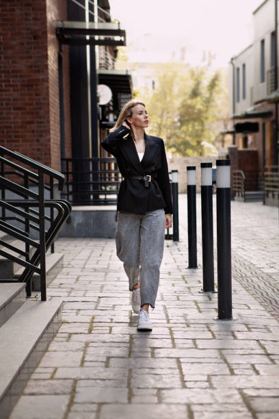 outfit fashion, young stylish woman wearing oversized black jacket, grey jeans and trendy white sneakers. urban fashion blogger walking street. autumn or spring style - spring fashion stock pictures, royalty-free photos & images
