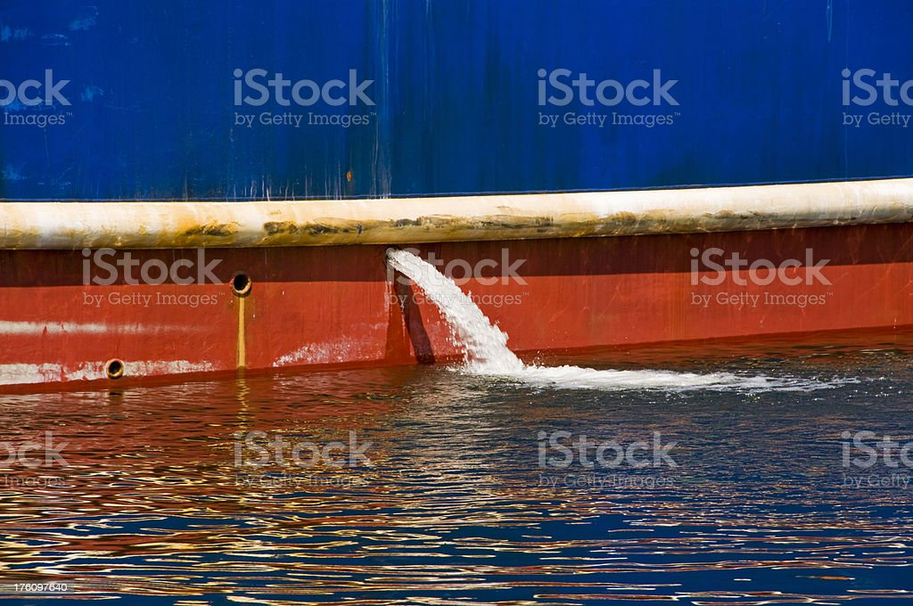 Outflow of ballast water from fishing ship's hull stock photo