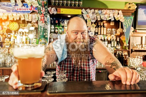 istock Outgoing fat male bartender giving beer 677518564