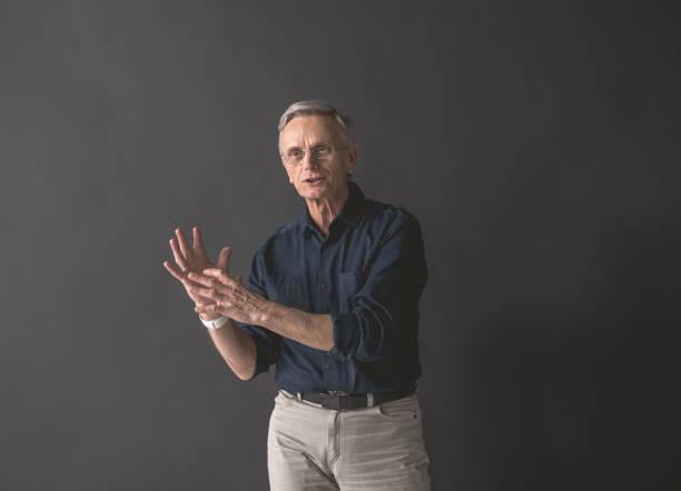 outgoing old man gesticulating hands - professore foto e immagini stock
