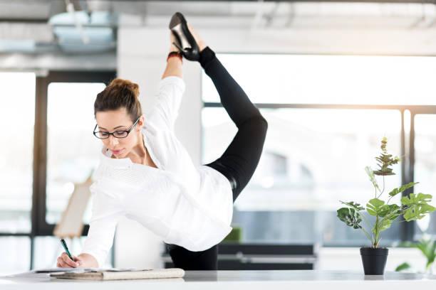 scheidenden sekretär gymnastik trainieren im büro - yoga fürs büro stock-fotos und bilder