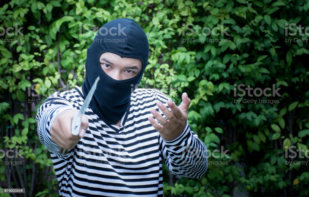 Outlaw bad man hold a knife pointing the target/Robber with knife and looking at camera stock photo