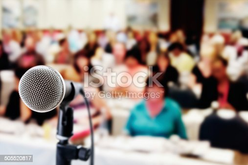 An old-fashioned vocal microphone in front of an out-of-focus audience at a meeting, seminar or social occasion.