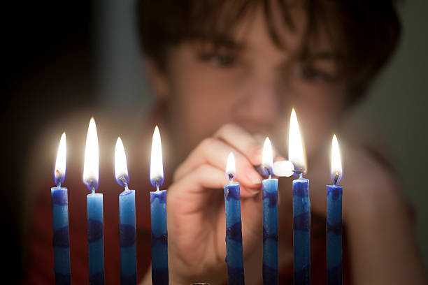 Out-of-focus boy lighting up a menorah in first plane Boy, age 8, lights the candles of the Hanukkah Menorah. judaism stock pictures, royalty-free photos & images