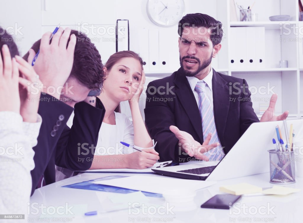 Outraged manager with colleagues at meeting stock photo