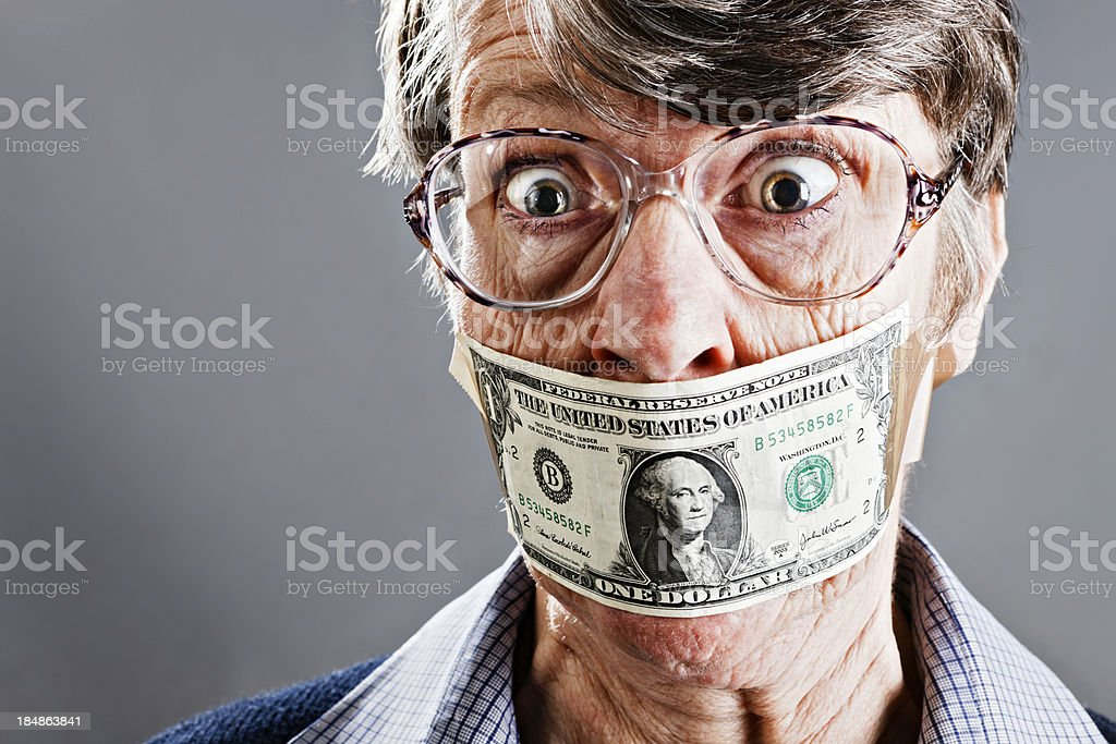 Outraged old woman gagged with dollar bill stock photo